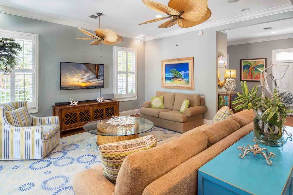 """The living area has a 60"""" flat screen TV and uniquely tropical overhead fans..."""