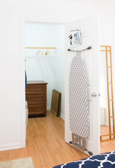Walk in closet with dresser and ironing supplies.