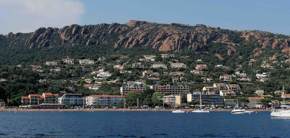 L'appartement est idéalement situé au centre de la baie d'Agay (immeuble jaune et ocre).