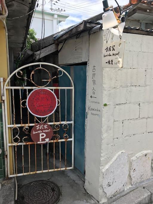 入り口。この赤い看板の扉の奥。鍵は暗証番号を入力してご自分で開けてください。