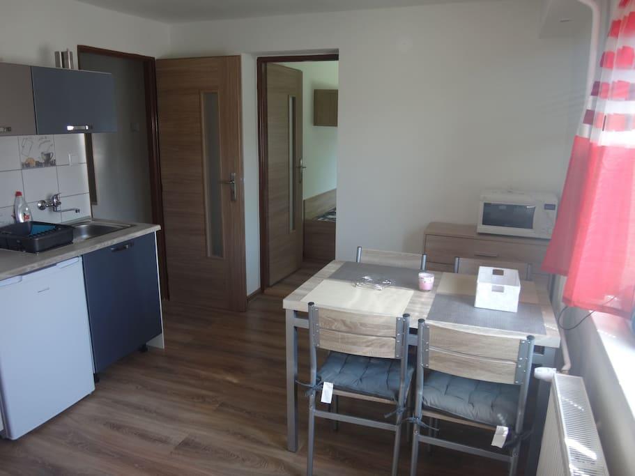 Obývacia miestnosť spojená s kuchyňou a vchodom do apartmánu