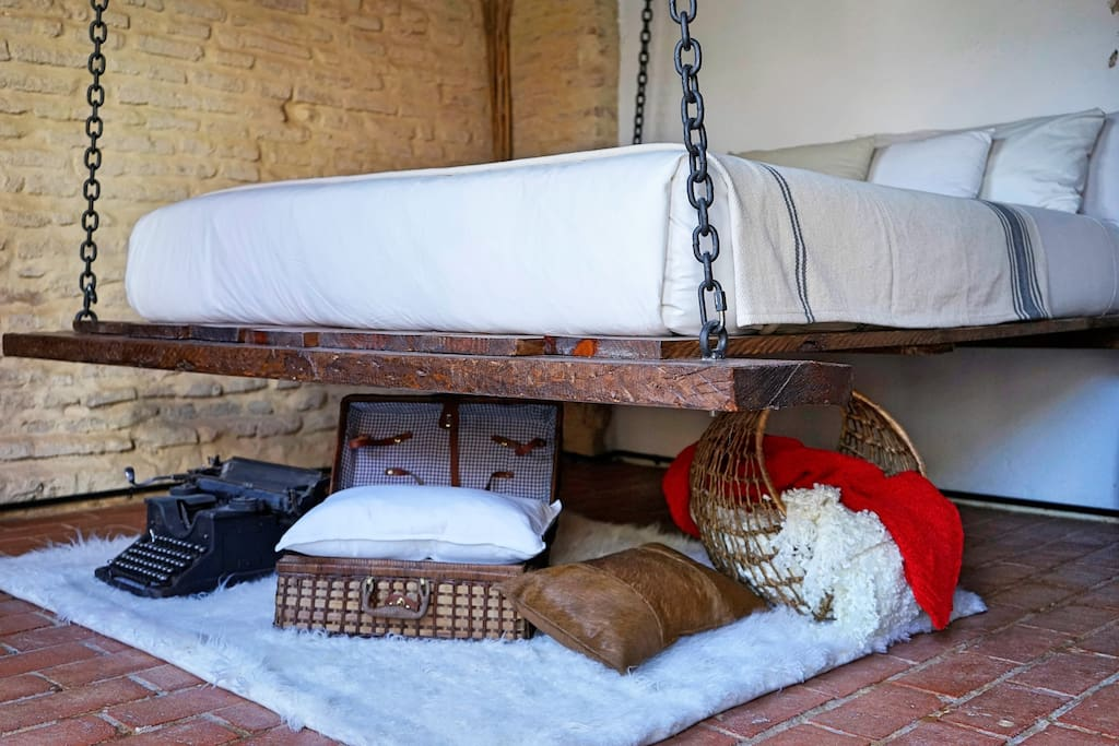 The real hanging bed anchored to the wood beam roof and a collection of goodies underneath the bed.