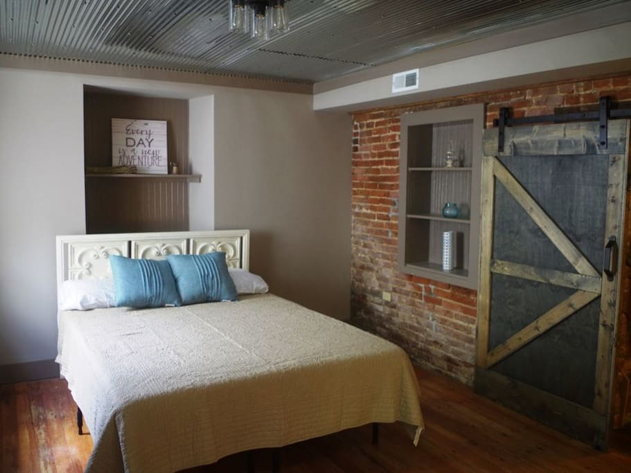 Downstairs bedroom w original exposed brick & sliding barn wood door