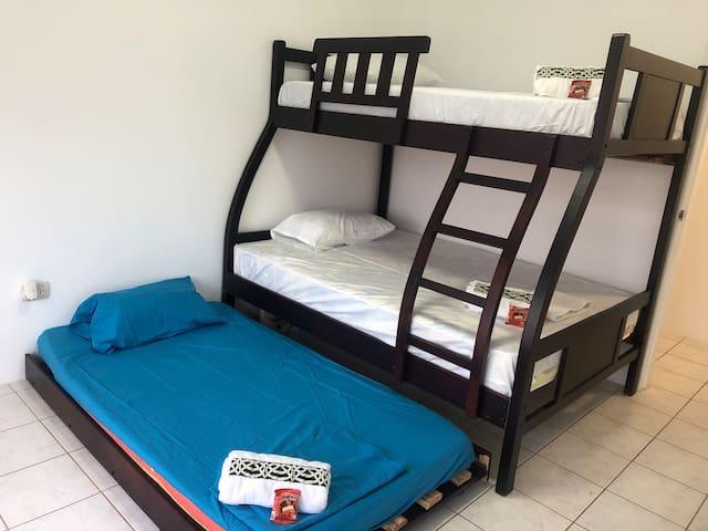 Dormitorio 1 con tres camas, persianas zebra y closets.