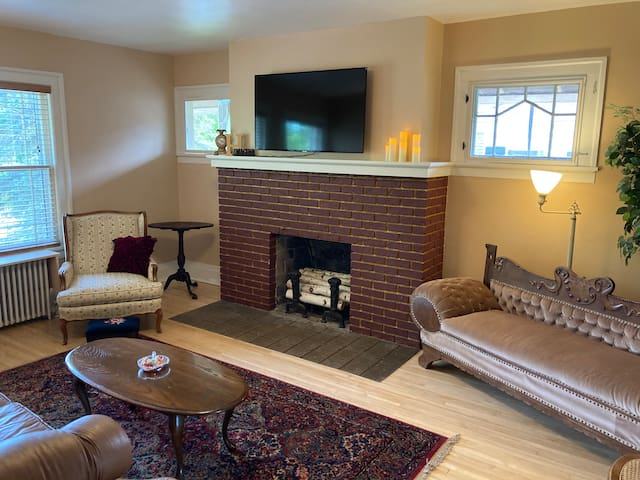 Living room with nonworking fireplace, couch, chair and antique chase lounge.  Smart TV with Netflix