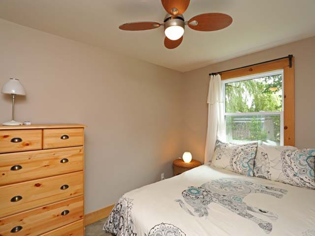 Bedroom 1 has a queen bed, dresser, 2 side tables, ceiling fan, mirror and armoire.