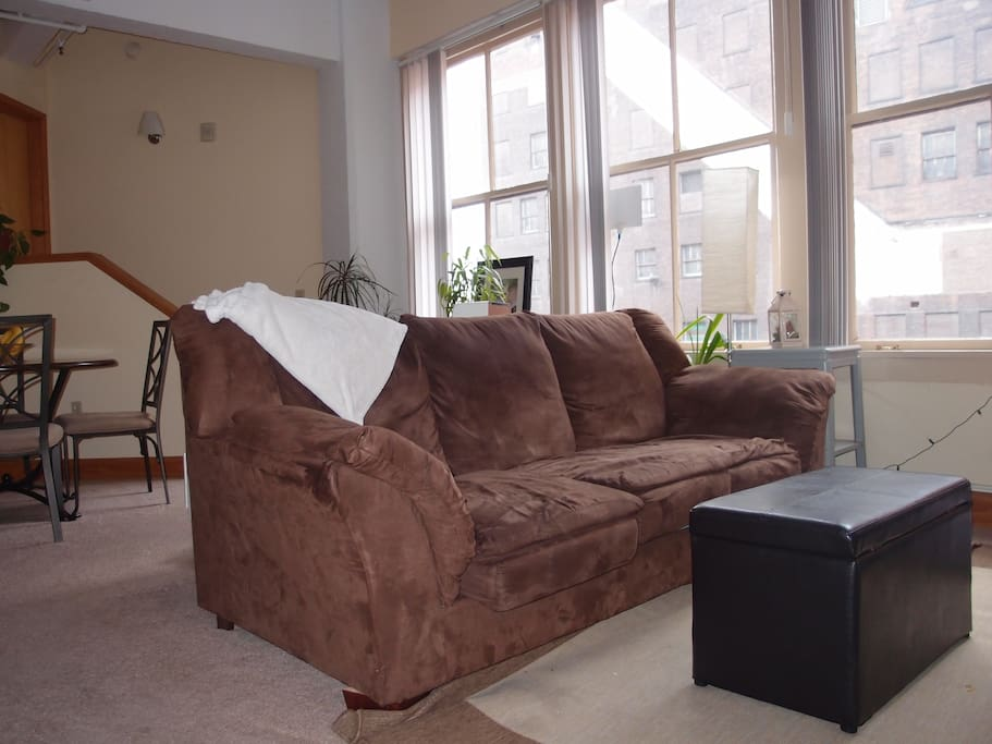 Comfortable couch with views of Tower City. Faces TV with Blu-ray player.