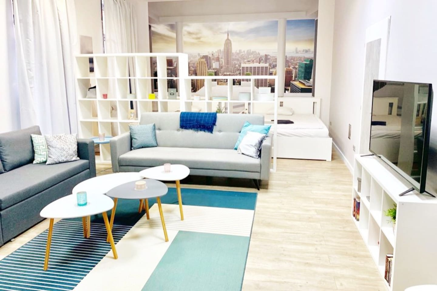 """One of 3 large suites in the flat, the """"New York"""" Suite features a 60"""" Smart TV (Netflix etc.), a large dining table, sofas that turn into beds, two queen size beds and a lounger chair. Four floor to ceiling windows face the wide and bright street."""
