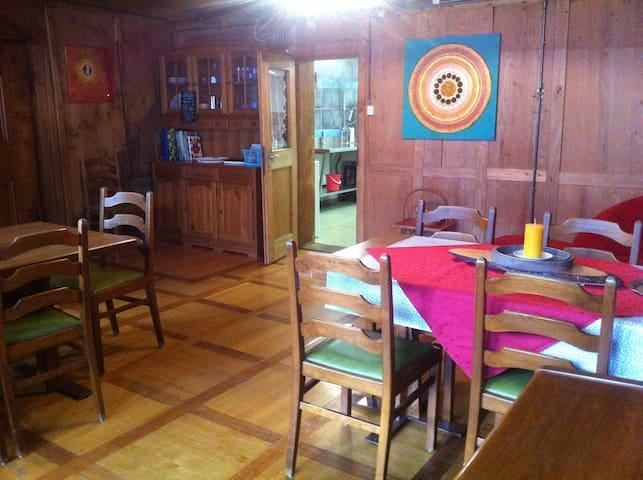 Der kleine Aufenthaltsraum mit Klavier, Sofa, Tischspiele und Seconhandbücher zum Schmöckern und Kaufen für Familien und Einzelgäste, gleich neben der Gastroküche.