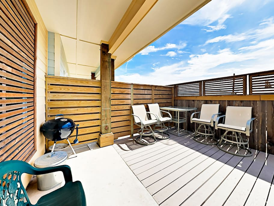 Step out onto the deck, which offers seating for 4 and a charcoal grill.