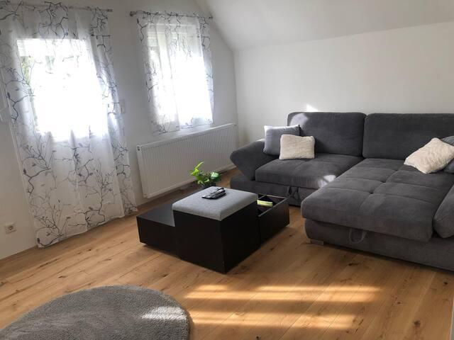 Wohnzimmer mit großer Couch, die sich mit wenigen Handgriffen in ein gemütliches Schlafsofa verwandelt.  Living room with a large couch that transforms into a comfortable sofa bed in just a few steps.