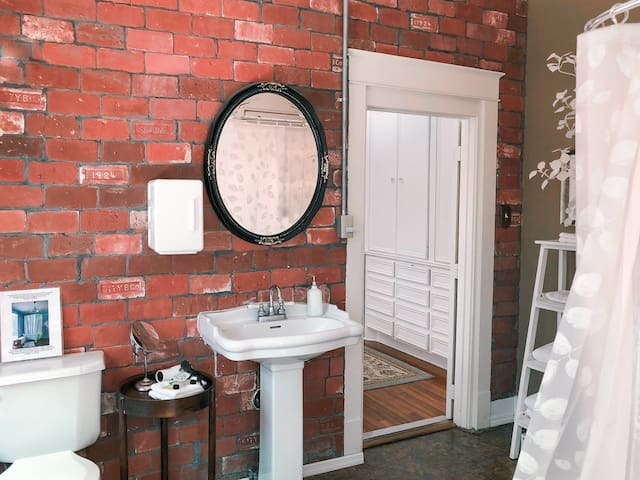 Private entrance takes you right into remodeled porch converted to large bath with clawfoot tub and exposed brick - note roomy storage in bedroom (french doors close for privacy)