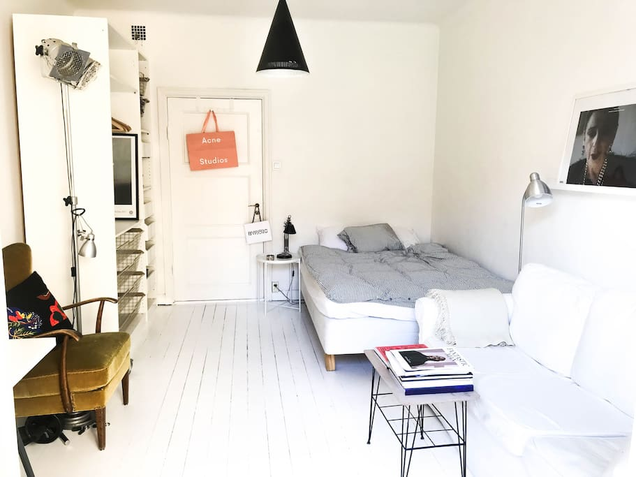 Big room with balcony, bed, sofa, wardrobe and desk.