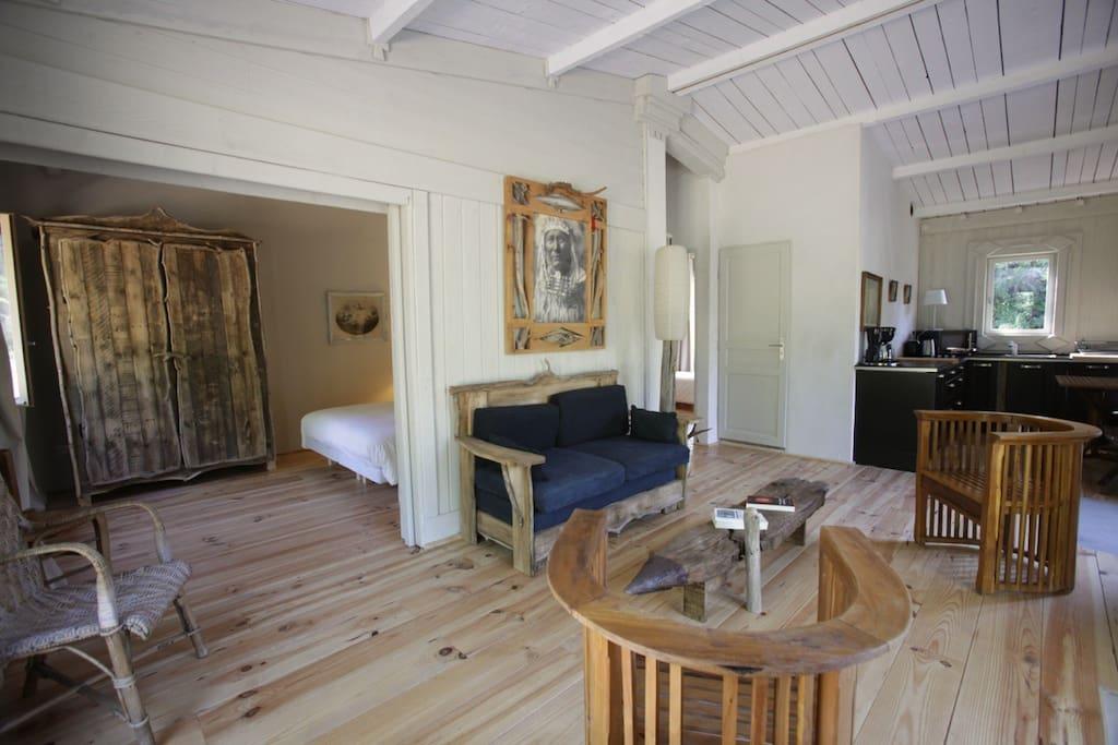 Vue du salon de la cabane du mont Paon donnant sur la chambre avec le lit double porte coulissante ouverte.
