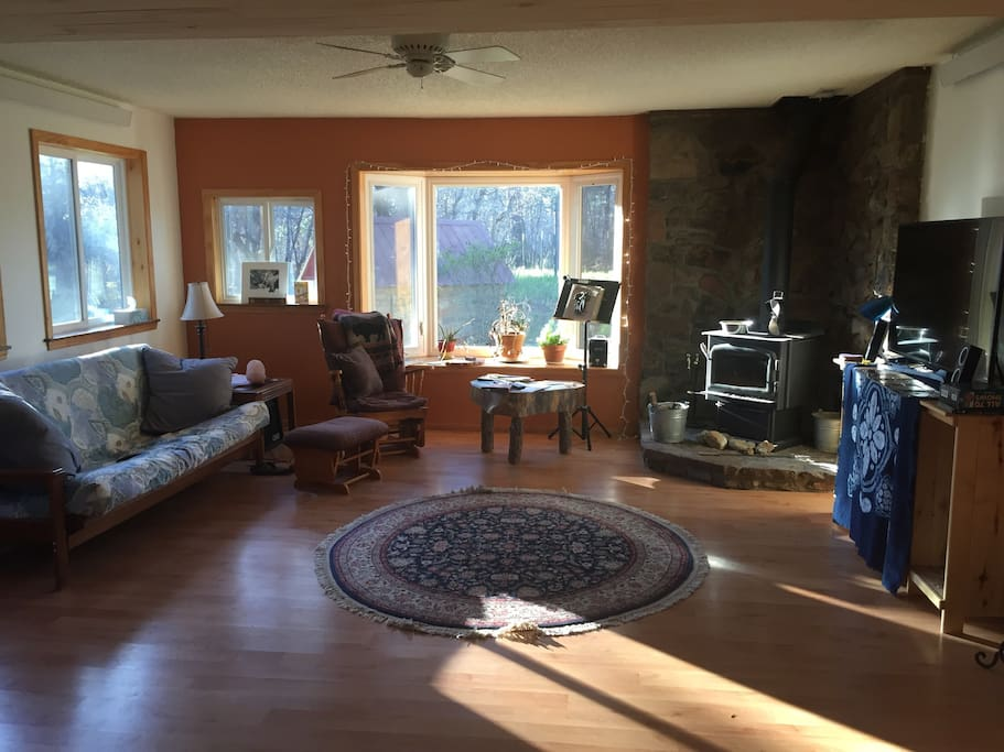 """Family room with sofa, 50"""" Ultra HDTV, blue-ray player, and wood-burning stove (please don't use without permission from owner).  This is common space which may be shared by owner or other renters."""