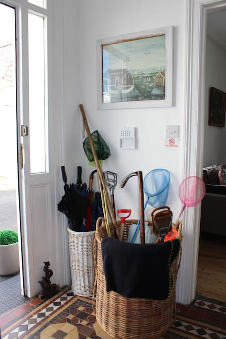 Baskets of walking sticks, umbrellas, fishing nets and more at the front door.