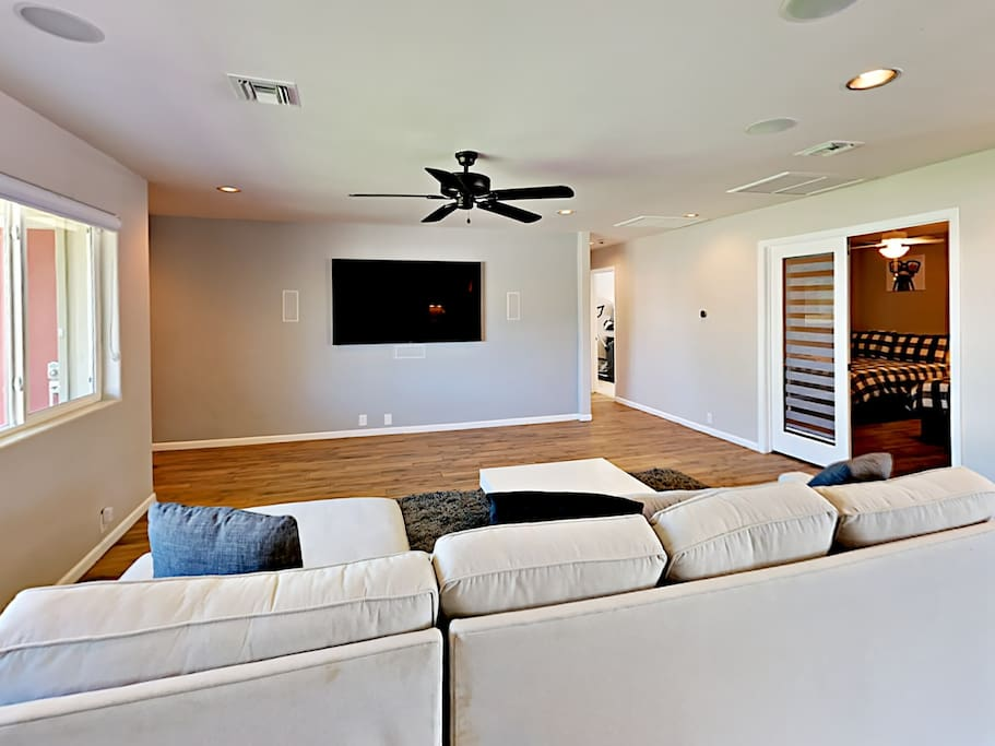 """Stretch out on the spacious sectional sofa and watch favorite shows on the 74"""" flat screen TV."""