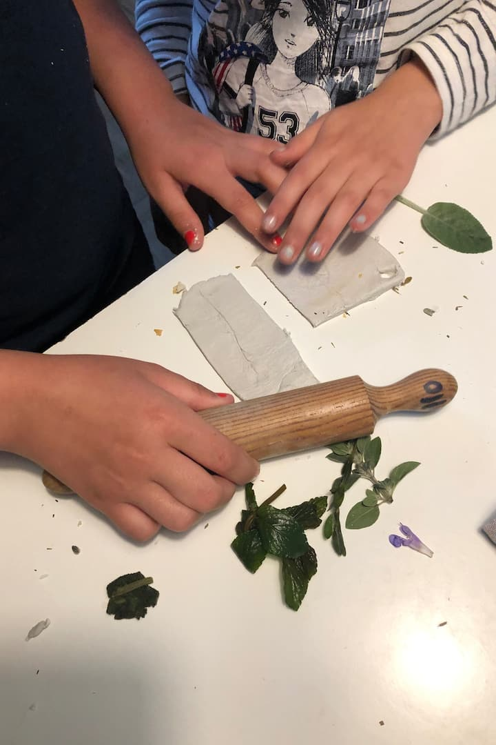 Children stamping their herbs onto clay