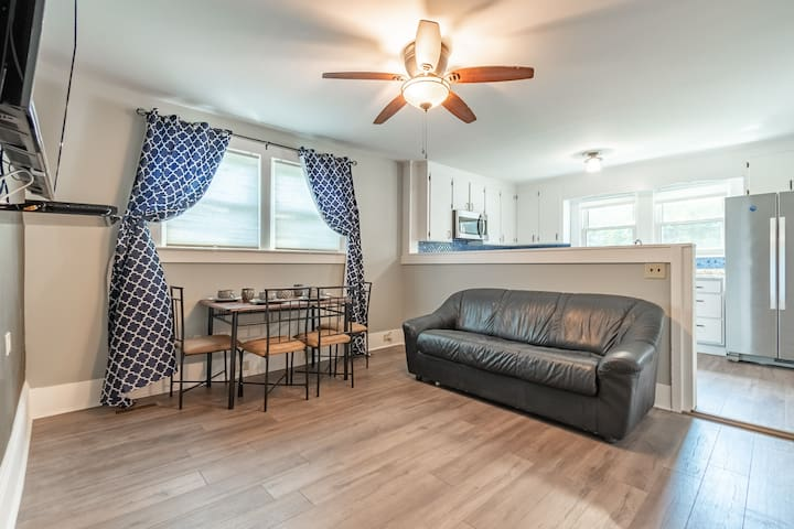 Living room has leather couch with pull-out full size bed, Roku tv, DVD player and small dining room table.