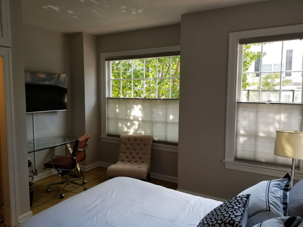 Heart of Georgetown BR: Work Desk, swivel chair, smart TV, comfort chair, and west windows partially shaded.