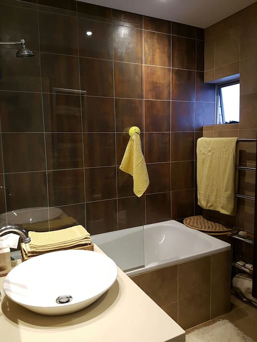 Bathroom with shower over bath, towels provided