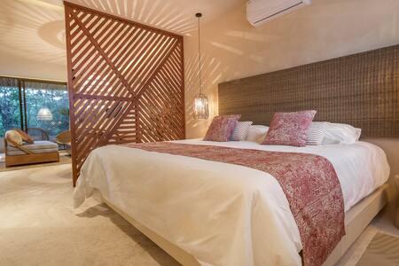 Cama king size con celosía de diseño que separa la zona del salón con sofá cama king size y vista de la terraza privada.