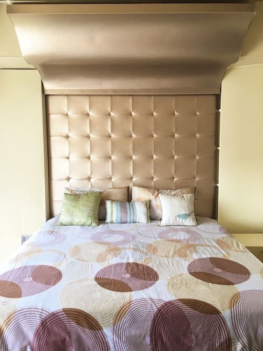 Full King Sized Bed with Padded Upholstered Tufted Rose Gold Synthetic Leather.