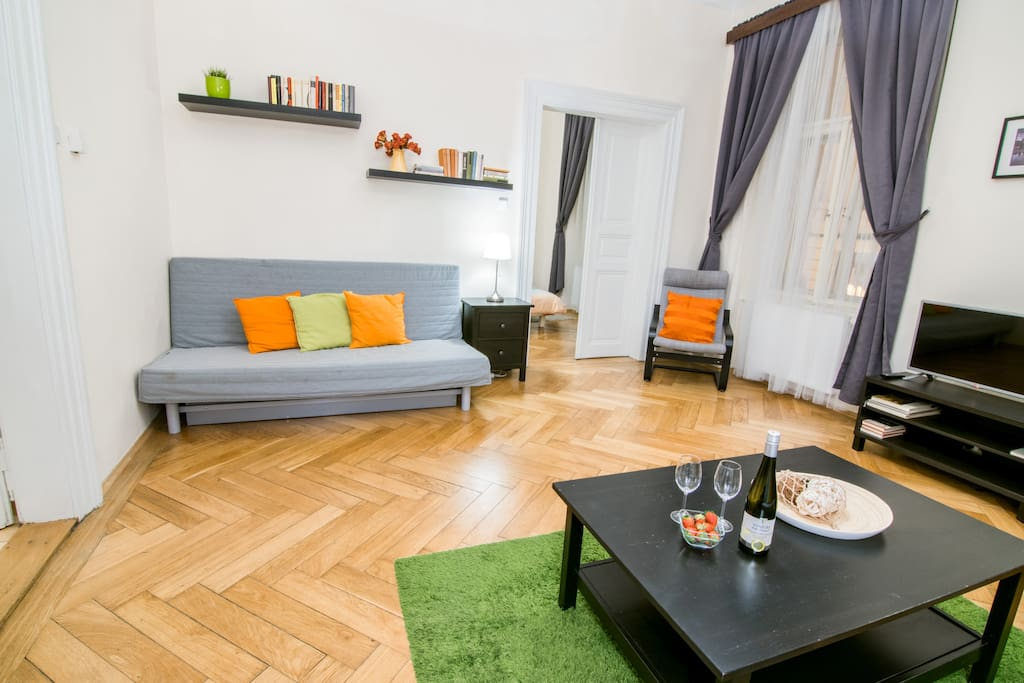A spacious living room with an original parquet floor. Equipped with two folding sofas, two armchairs and television