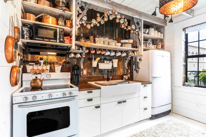 In the barn's kitchen, there is an electric stove/oven, microwave, vintage refrigerator, garbage disposal and double-bowl farmhouse sink. Counters are upcycled barn wood & the wall has upcycled corrugated metal from a local ranch.