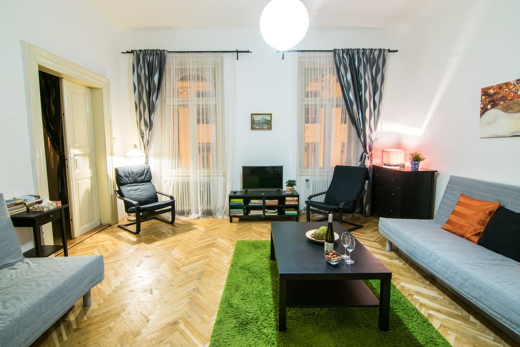 A spacious living room with an original parquet floor. Equipped with two folding sofas, two armchairs, television and wardrobe.