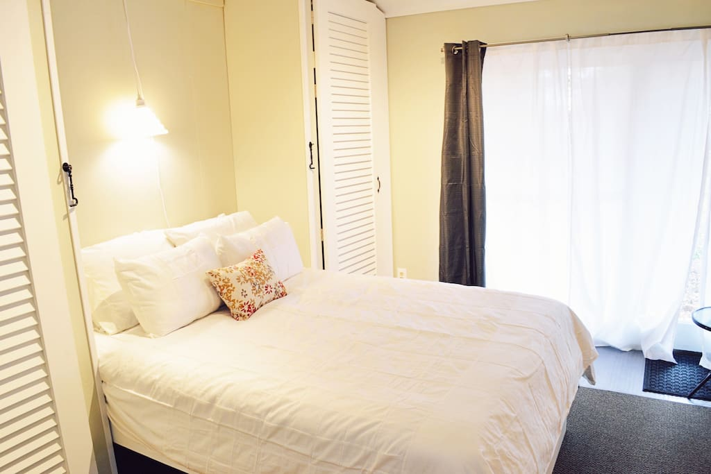 Queen size Murphy bed with seating area with private door and backyard access.