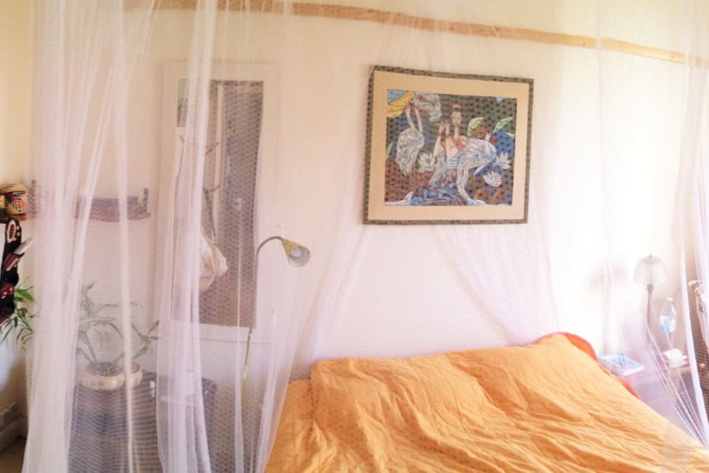 The bedroom with a mosquito net and a big closet