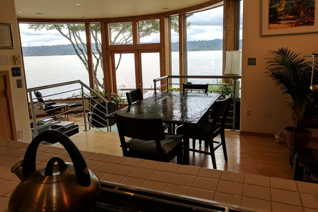 Dining and living rooms from kitchen, looking out over lake.