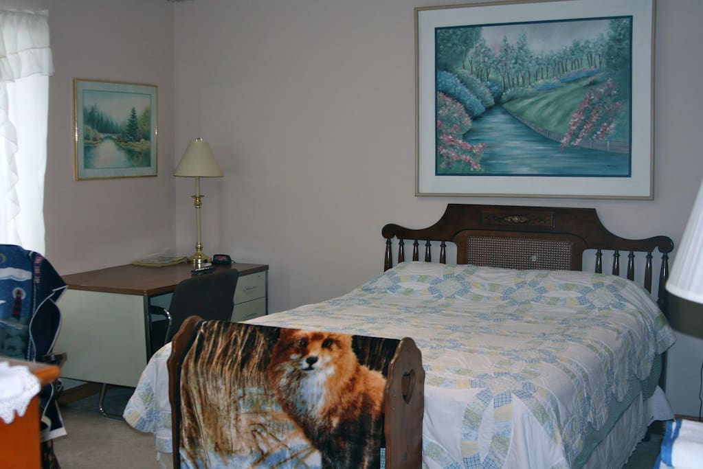 Nice bedroom with full bed, rocking chair, dresser, closet, cable TV, WiFi internet, and a desk.