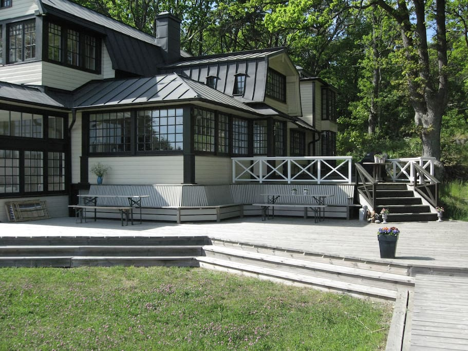 The house is surrounded by a large wooden deck