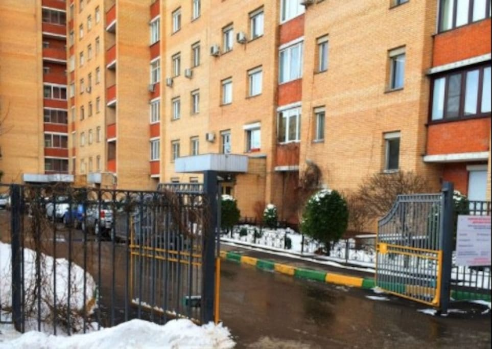 The entrance to the house and the parking lot. The house is a guarded apartment building // Вход к подъезду и на парковку. Дом охраняемый.