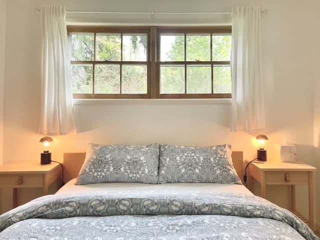 Bedroom with queen bed. There is also a wireless phone charger.