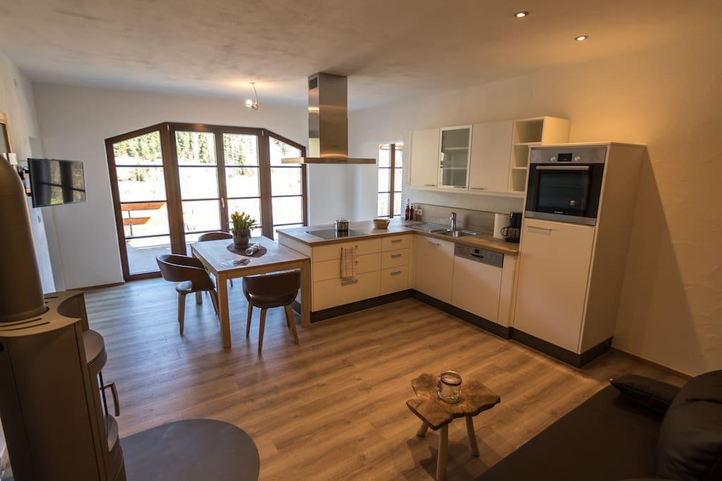 Wohn-Essbereich mit Kaminofen und Sofa, modernen Flachbild-Fernseher, hochwertig ausgestattete Küche mit  Spülmaschine