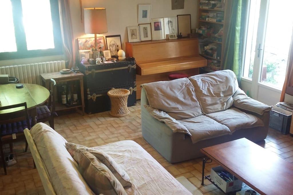 Salon avec au 1er plan canapé-lit et piano au fond à droite