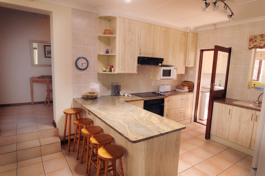 Kitchen with door onto scullery (dishwasher, washing machine and dryer), 2 fridges, oven, stove top & microwave.