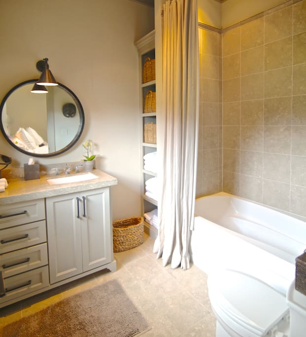 Bathroom with deep soaking tub and shower, Limestone counter tops and tiles, fully stocked with plush cotton towels and bathrobes.  Stocked with amenities  for your stay.