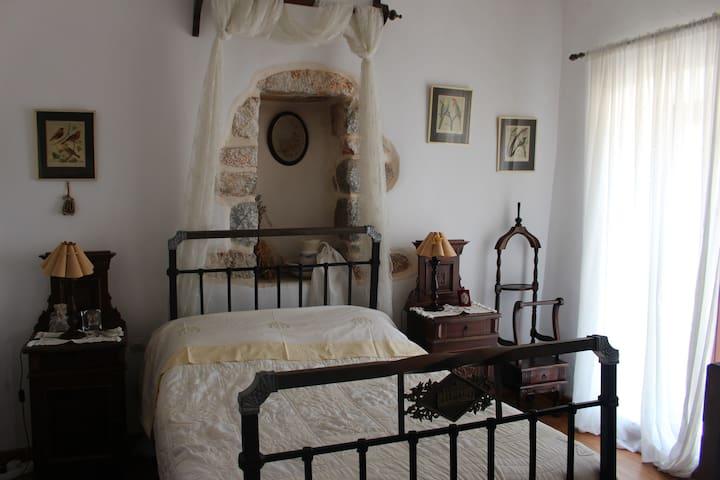 Κρεβατοκαμαρα δευτερου πατωματος , διπλο κρεβατι  με επιπλα αντικες του 1800.