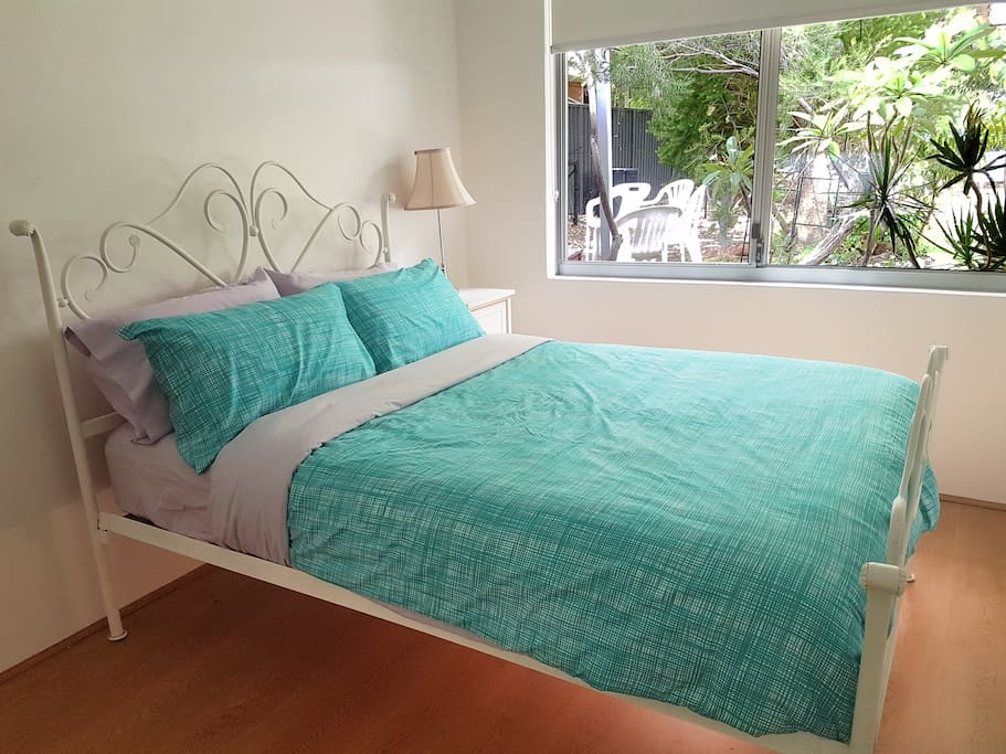 Bedroom with double bed and garden view.