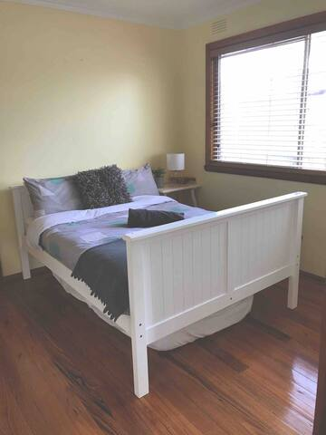 This room has a double wooden bed. There is a single mattress stored under the bed for guests to use. There is also a wooden rack to hang your clothes on in this room.
