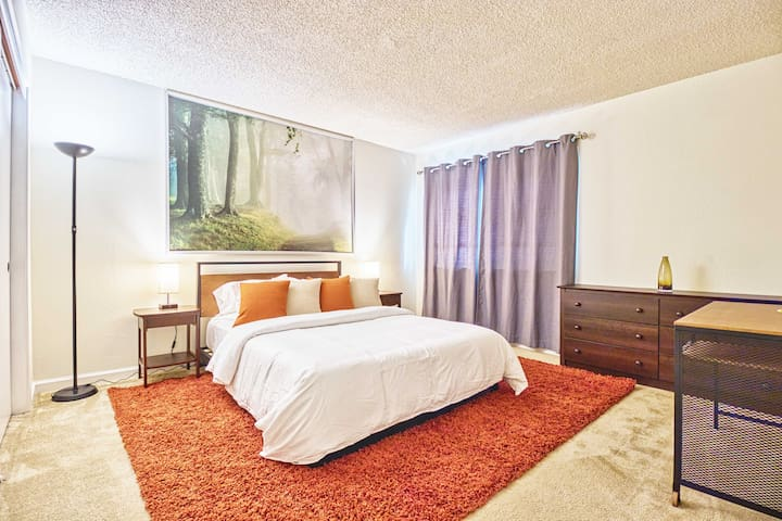 The master bedroom is spacious with a queen bed, memory foam mattress, new comforter, comfy throw pillows and nice wall art