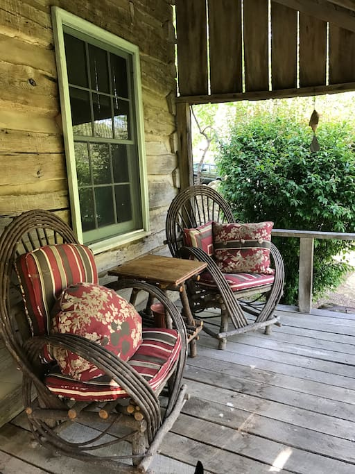 The front porch has two chairs and two rivers and a small table for front porch sittin'