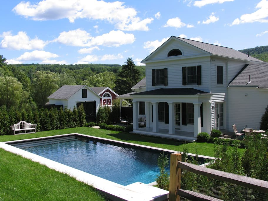 Poolhouse and private, heated pool with view of ping pong house and barn