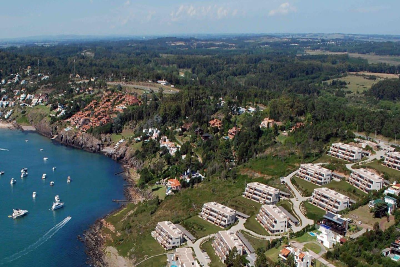 Vista aérea del complejo Quartier Punta Ballena y de las embarcaciones ancladas en la bahía. El departamento está situado en la villa superior a la izquierda de la imagen.