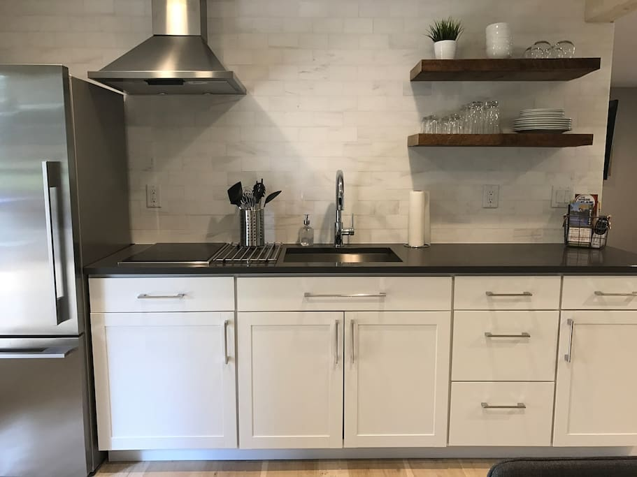 Cute new kitchen with a full sized refrigerator, cooktop, microwave & countertop oven for minimal cooking/baking.  Note: no built in conventional oven or dishwasher.