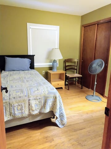 Room with single bed and fan